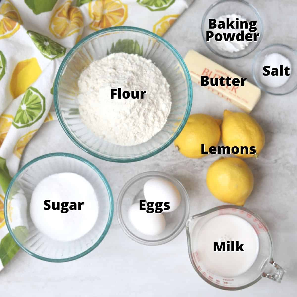 Ingredients for lemon bread labeled on white counter.