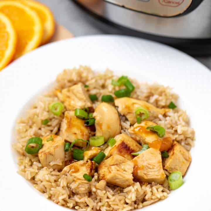 Orange Chicken served over rice next to instant pot.