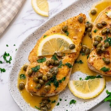 Chicken breast topped with lemon slices and piccata sauce on white platter.