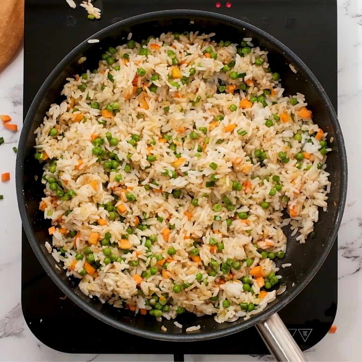 Rice with carrots and peas in large skillet.