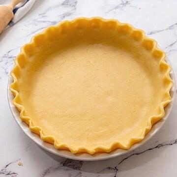 Unbaked pie crust in white pie dish.