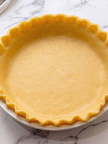 Unbaked pie crust in white pie dish.