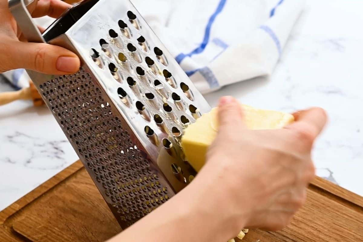 Using a box grater to grate butter for pie crust.
