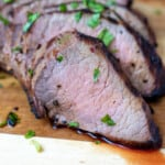Close up of sliced london broil on wooden cutting board.