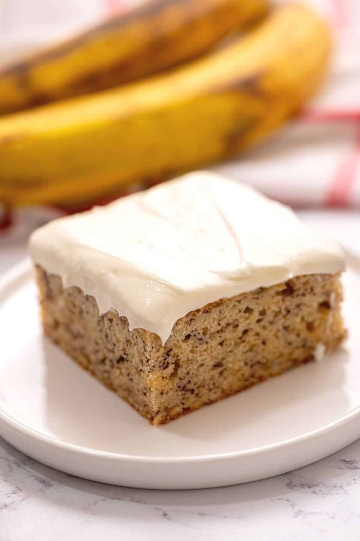 Slice of banana cake with cream cheese frosting on white plate.