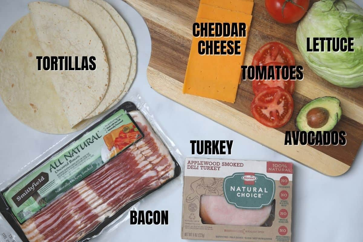 Labeled ingredients for turkey club wraps on white counter.