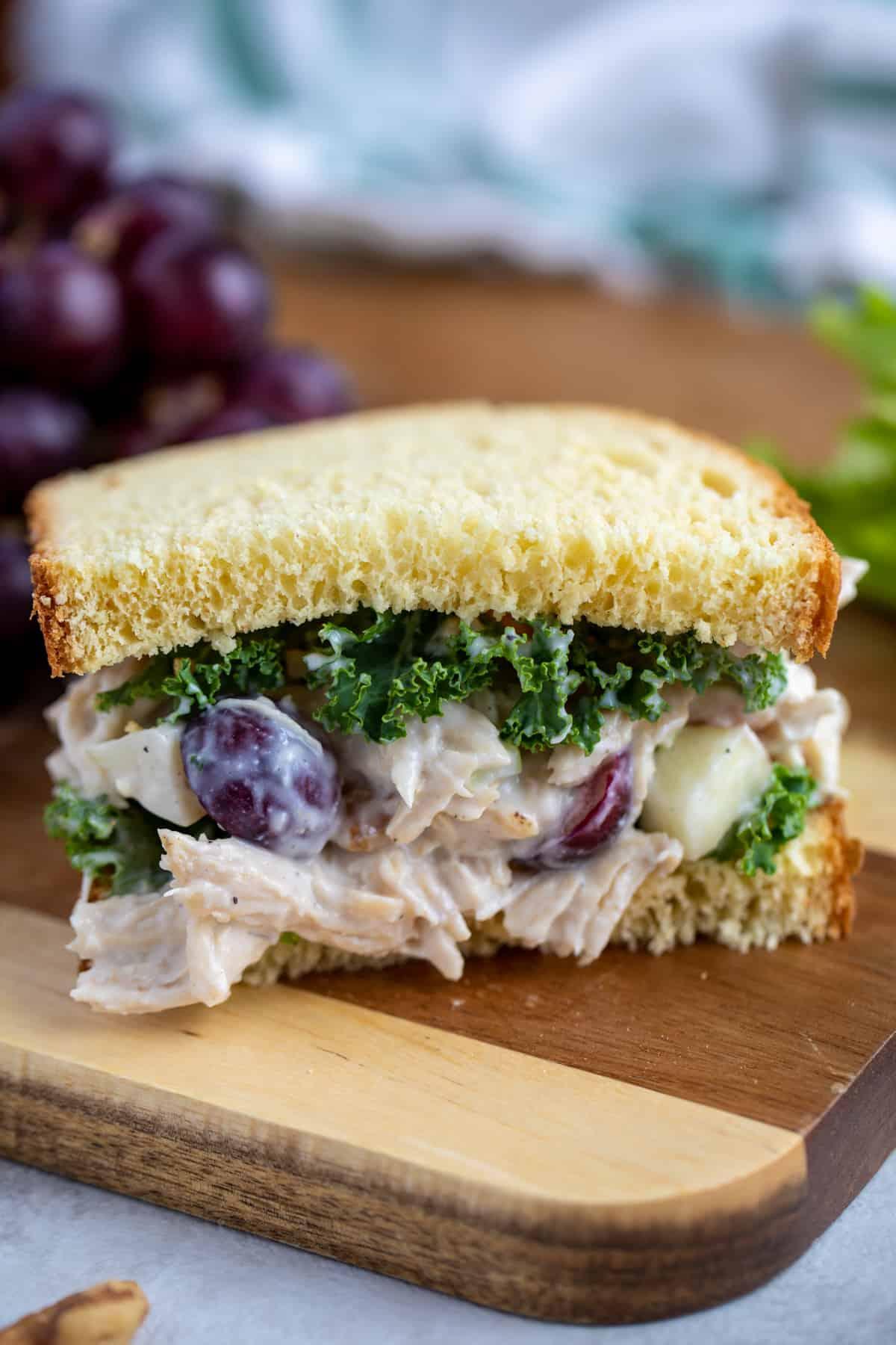 Waldorf Chicken Salad Sandwich on cutting board.