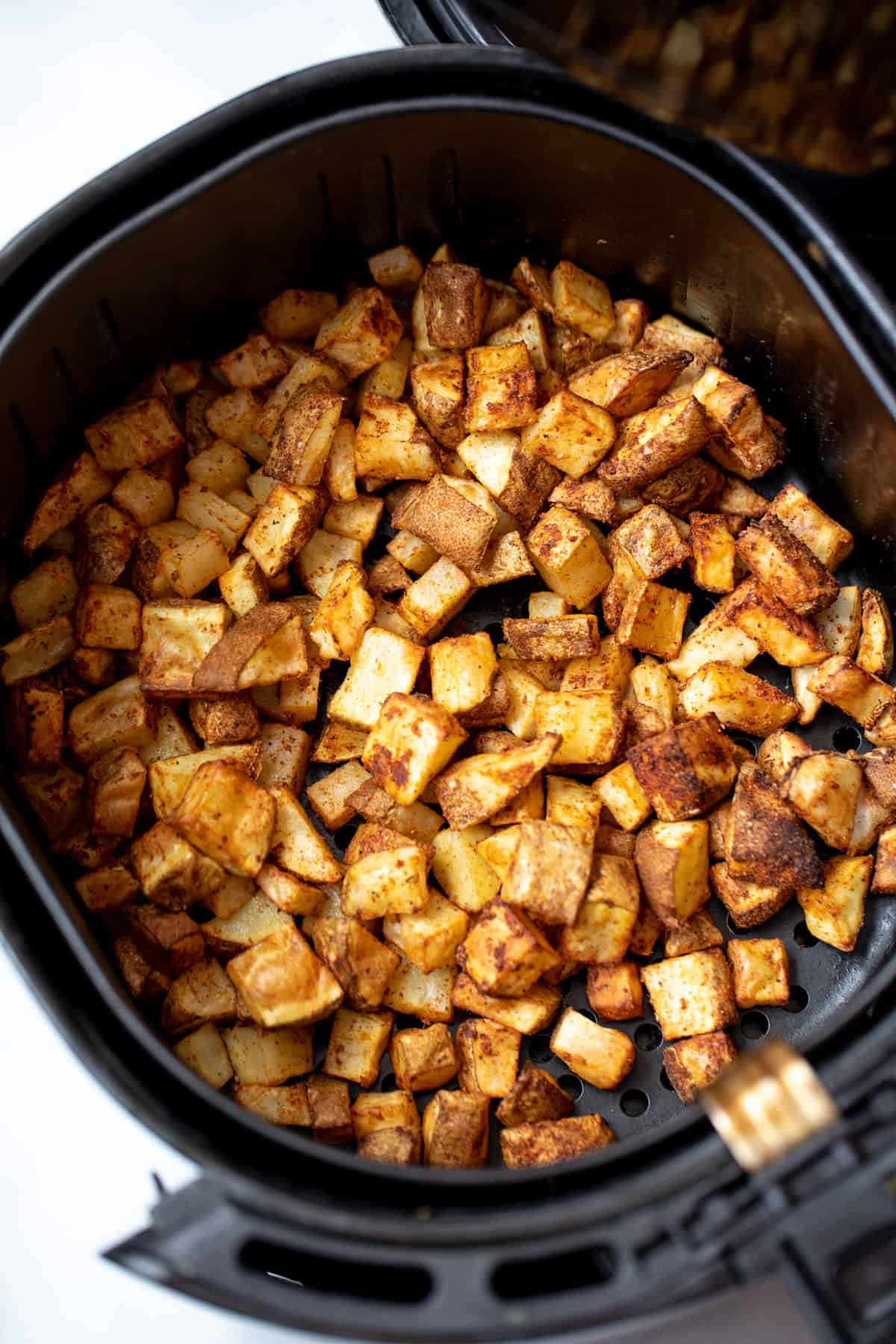 Air Fryer Basket with cubed seasoned potatoes.