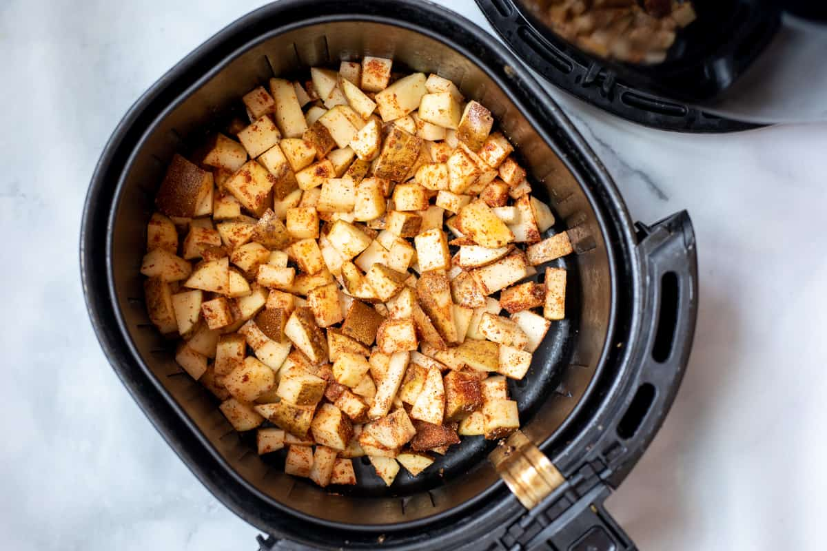 Cubed potatoes spread out in air fryer basket.
