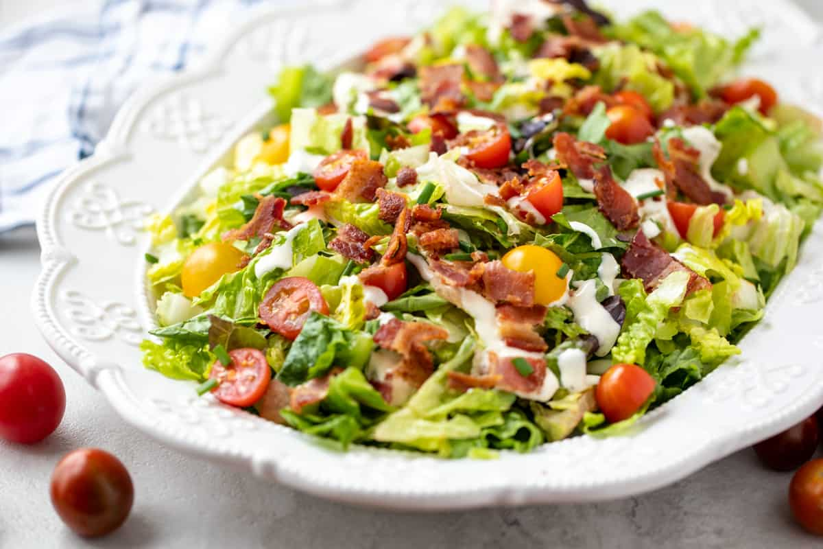 White Platter with BLT Salad drizzled with ranch dressing.