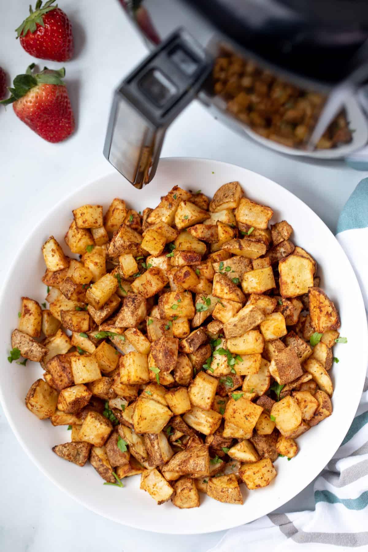 Bowl of crispy potato cubes next to air fryer.