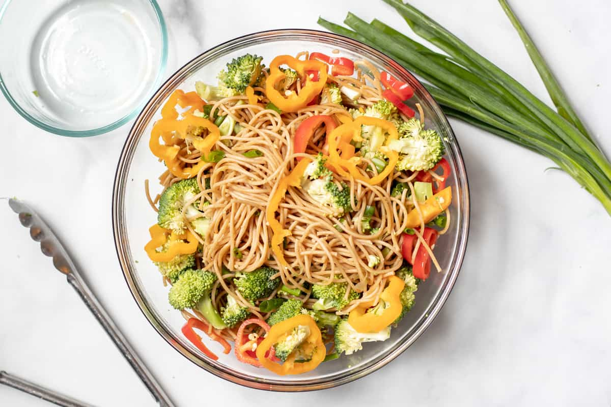 Noodles, vegetables, and sesame dressing tossed together in clear mixing bowl.