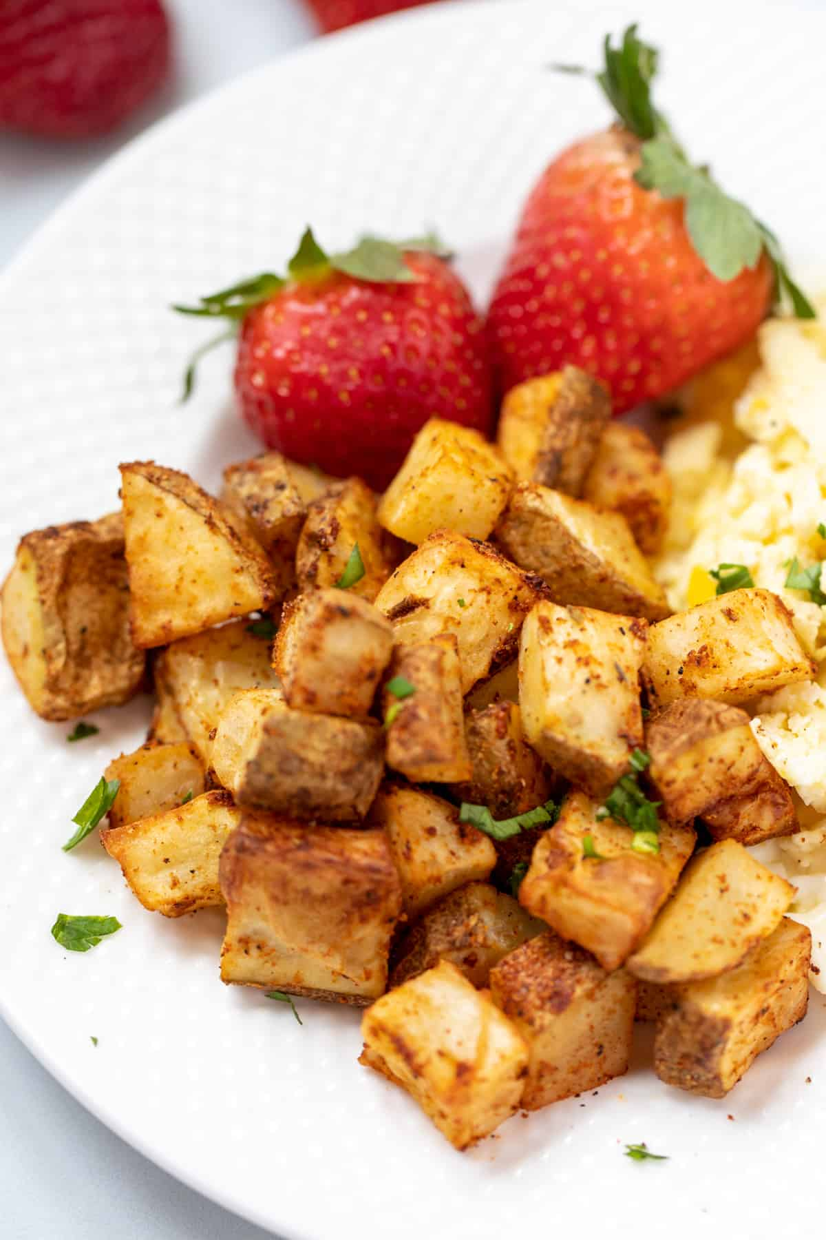 Air Fryer Hashbrown Potatoes on white plate next to scrambled eggs.