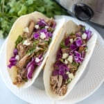 2 Pork tacos on white plate made with Slow Cooker Carnitas.