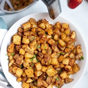 Bowl of Crispy potatoes next to air fryer.