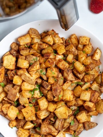 Bowl of Crispy potatoes next to air fryer.