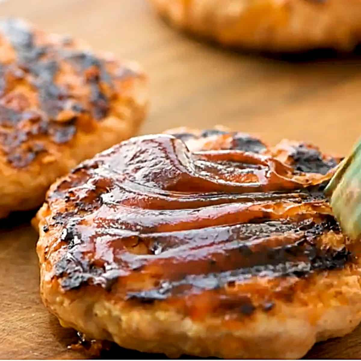 Barbecue sauce being brushed over chicken burgers.