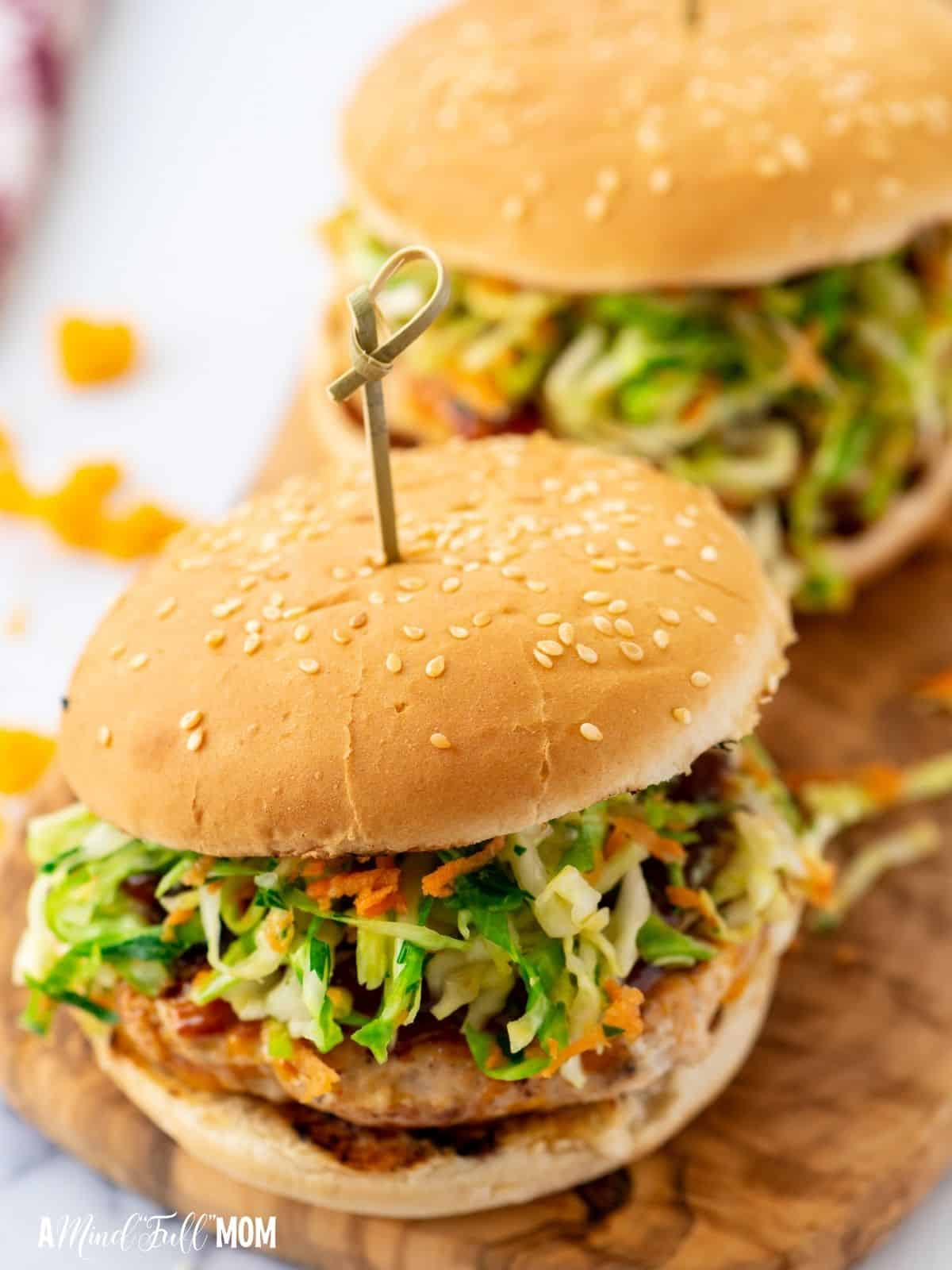 Two chicken burgers topped with coleslaw on wooden cutting board.