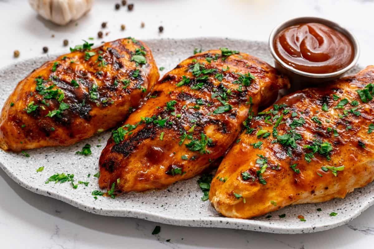 Grilled BBQ Chicken on white platter topped with parsley.