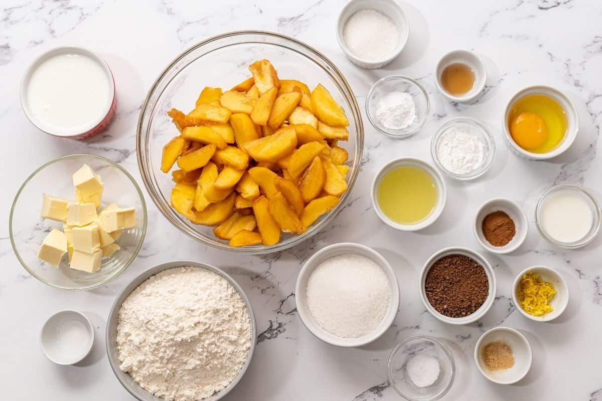 Ingredients for peach cobbler on white counter.