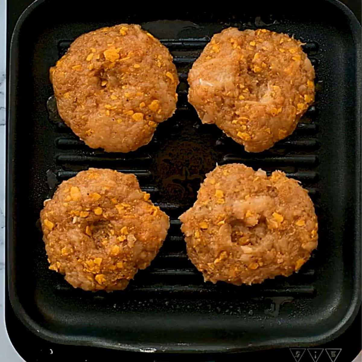 Four chicken burger patties on grill top.