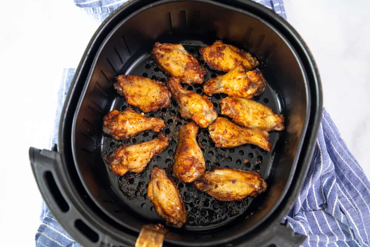 Crispy chicken wings in air fryer basket.