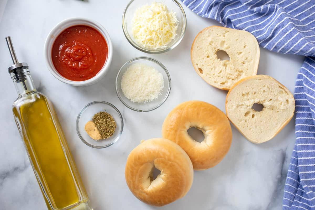 Ingredients for bagel pizzas on counter.