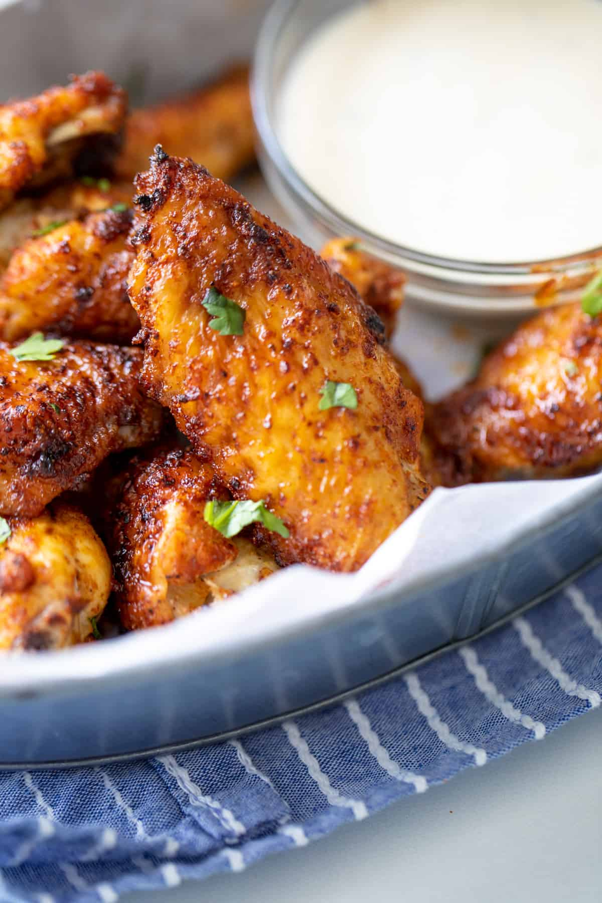 Close up of dry rubbed air fryer wings in a silver basket.