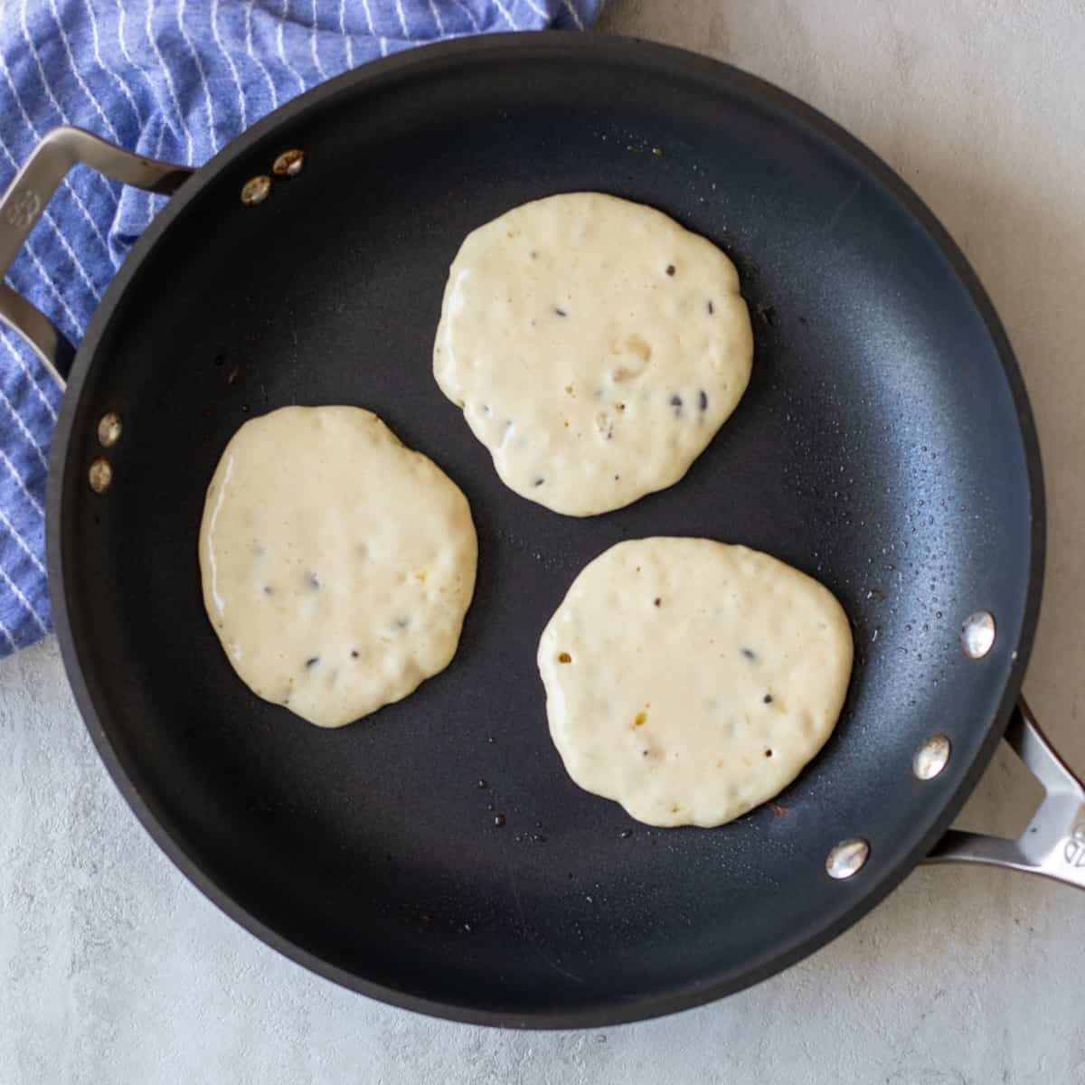 3 chocolate chip pancakes in skillet.