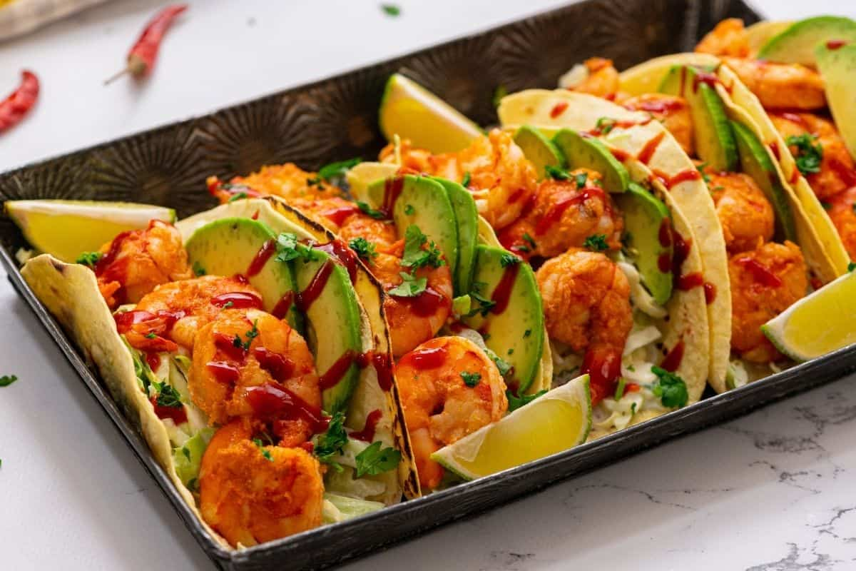 Shrimp tacos on serving platter drizzled with hot sauce.