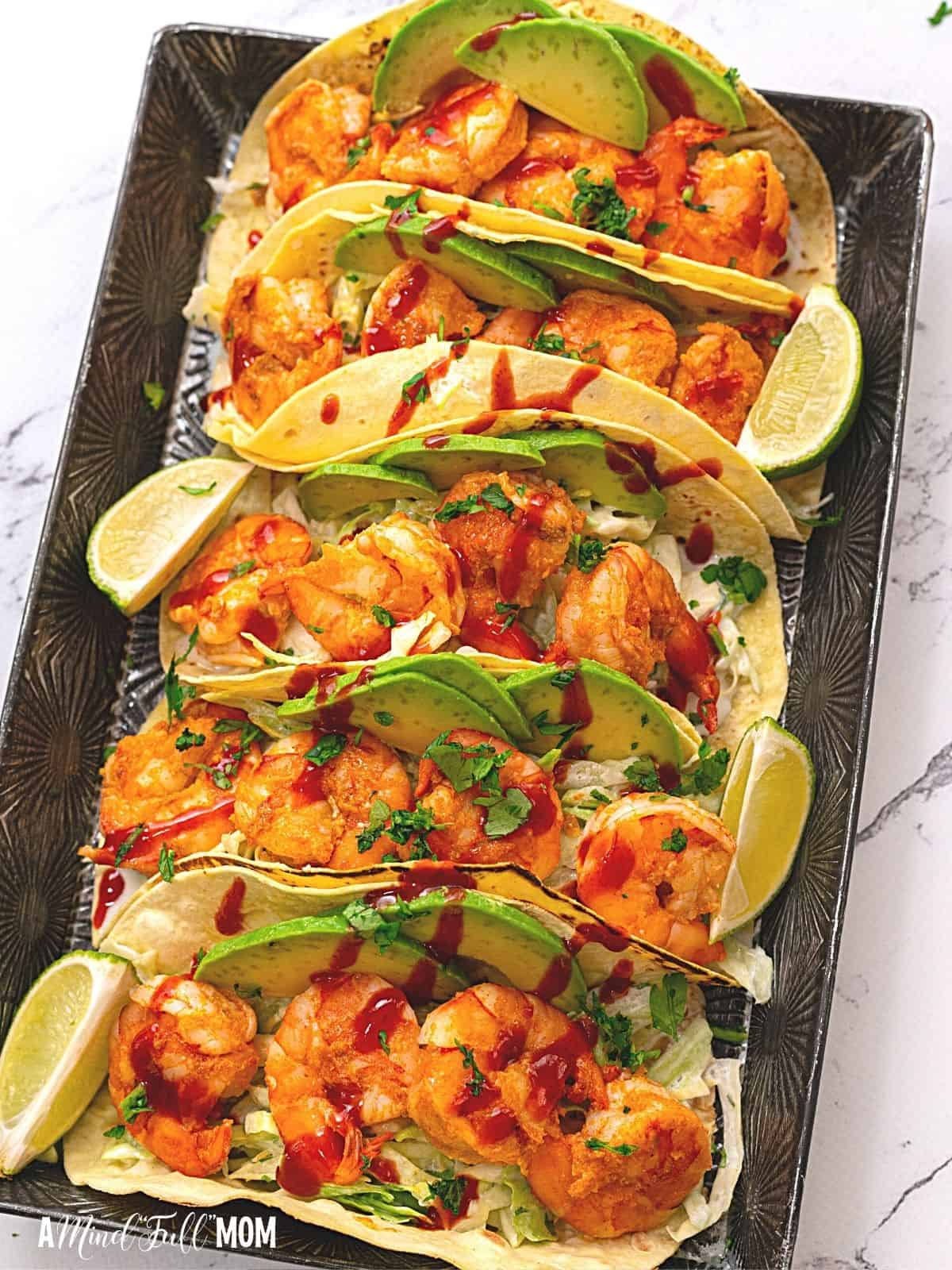 4 assembled shrimp tacos with avocado and slaw.
