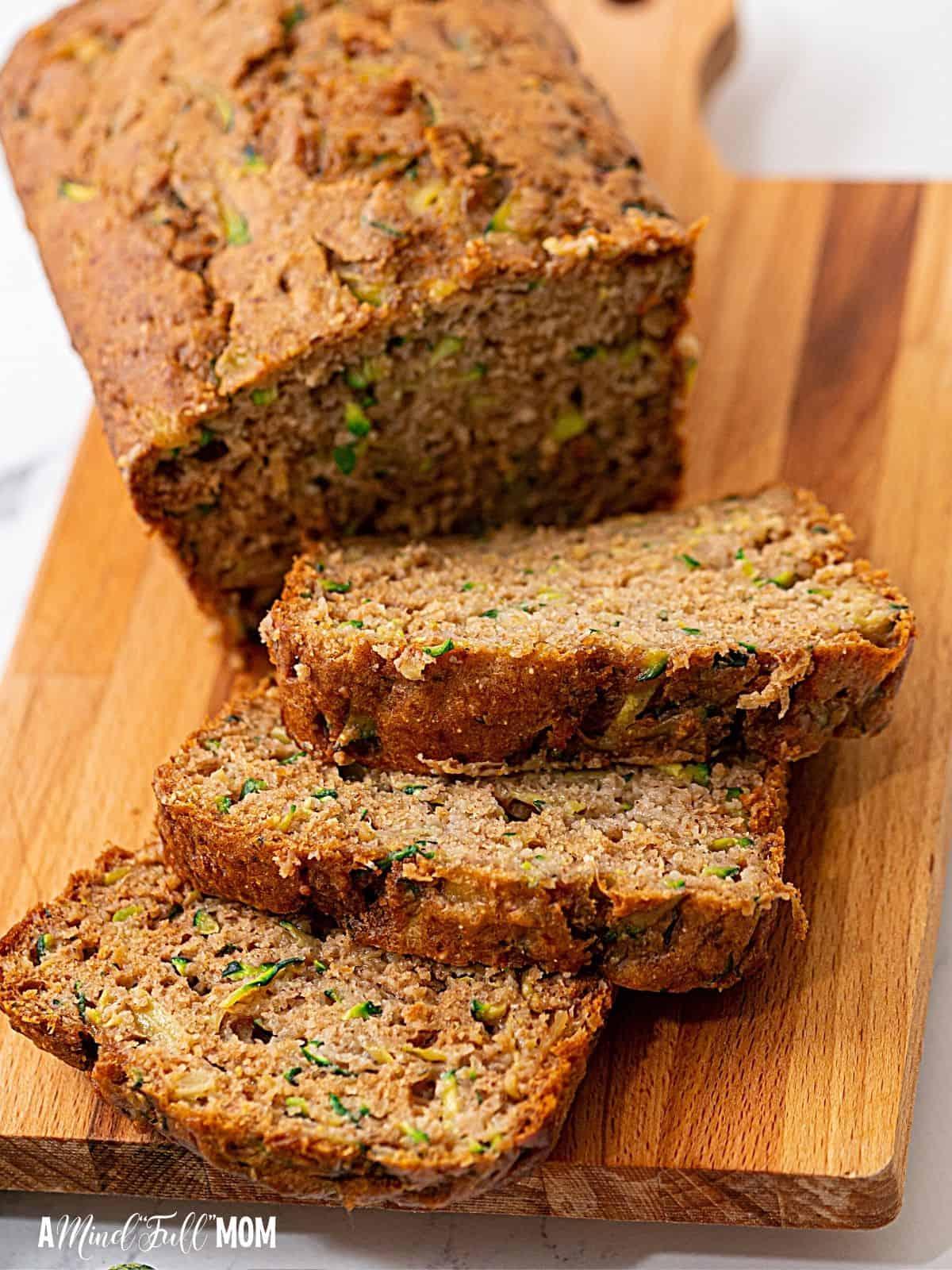 Sliced zucchini bread on wooden cutting board.