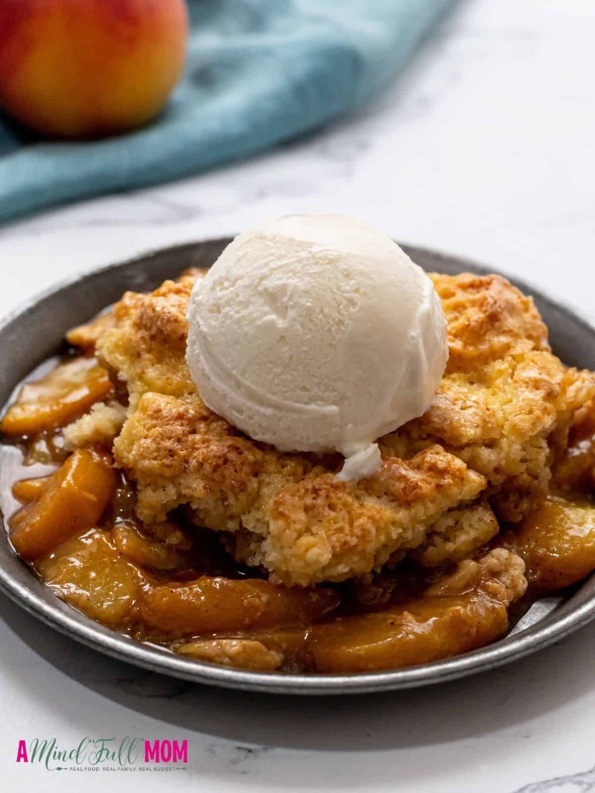 Peach Cobbler dished out on silver plate and topped with a scoop of vanilla ice cream.
