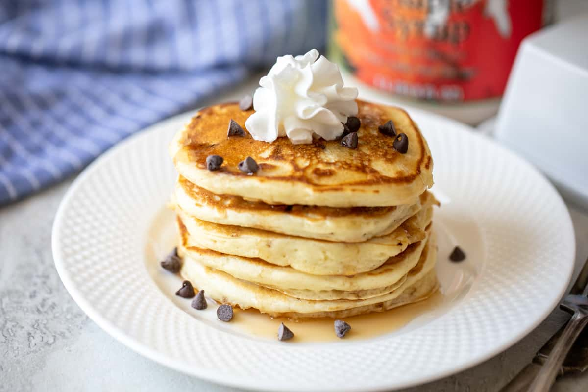 Stack of chocolate chip panakes with syrup and whipped cream.