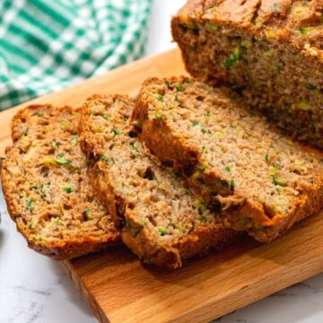 Close up of sliced zucchini bread on wooden cutting board.