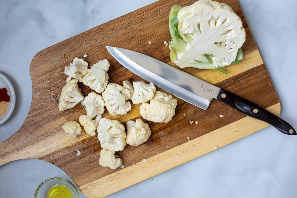Cauliflower on chopping board cut into florets.