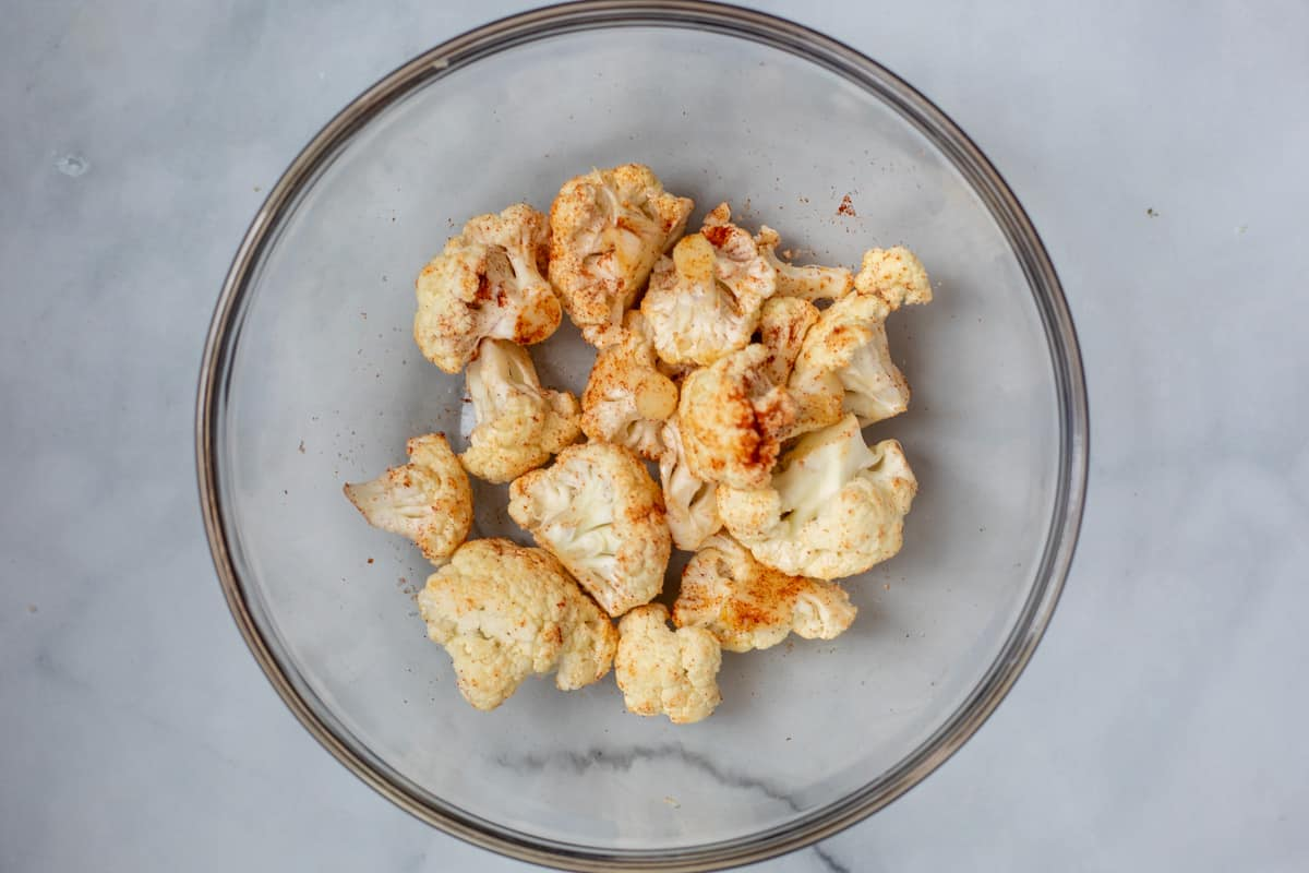 Seasoned cauliflower in mixing bowl.