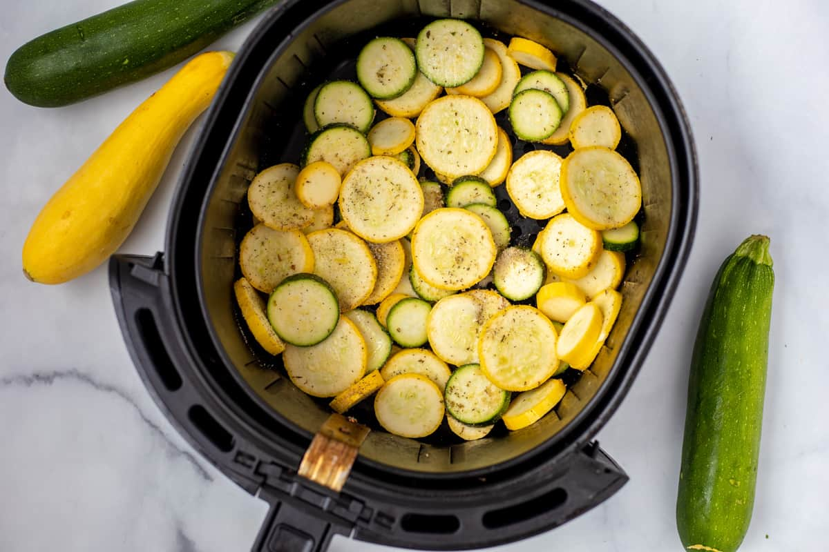 Sliced zucchini and squash in basket of air fryer.