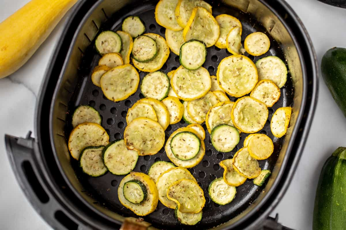 Squash and Zucchini Slices in basket of air fryer.