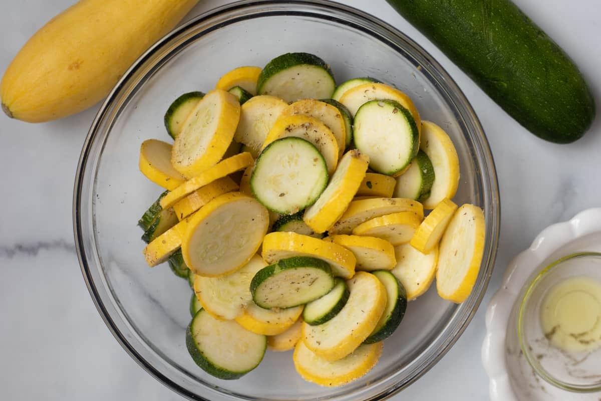 Sliced squash in bowl with seasonings.