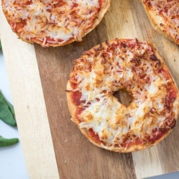 Bagel Pizza on wooden cutting board.