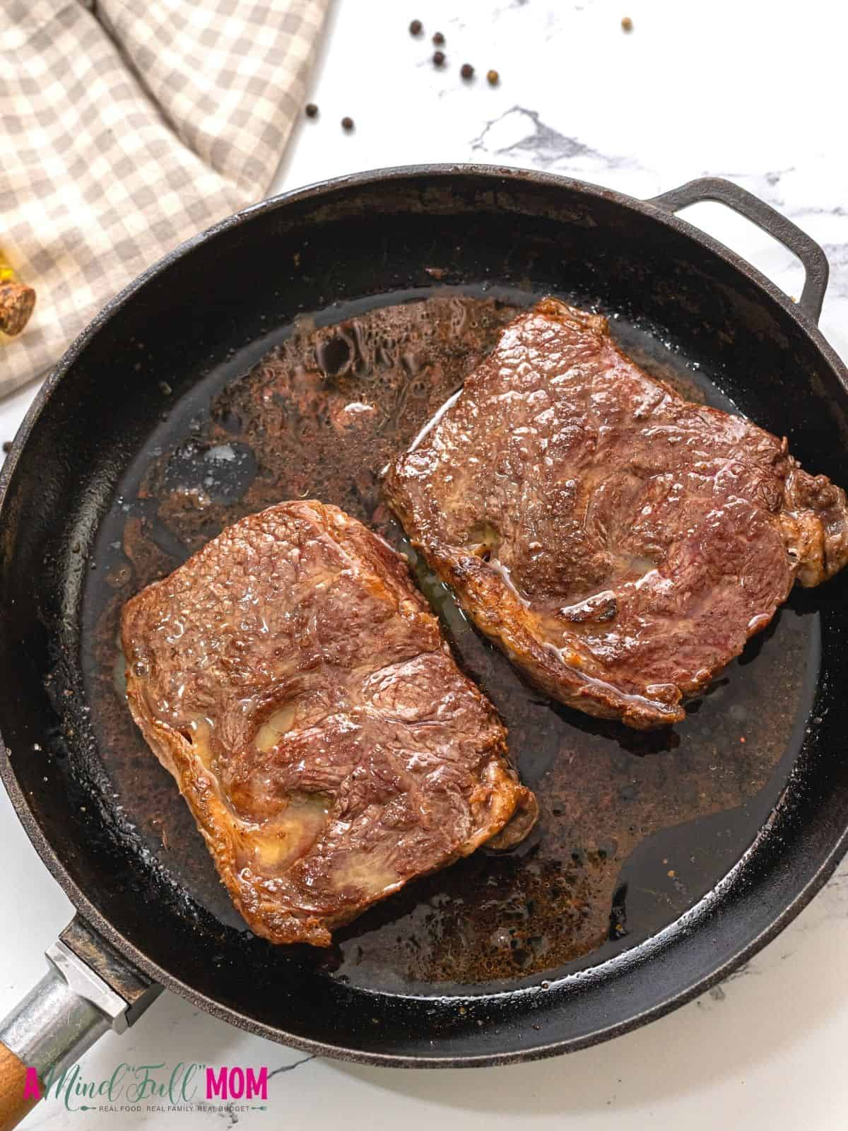 2 cooked ribeyes in cast iron skillet.