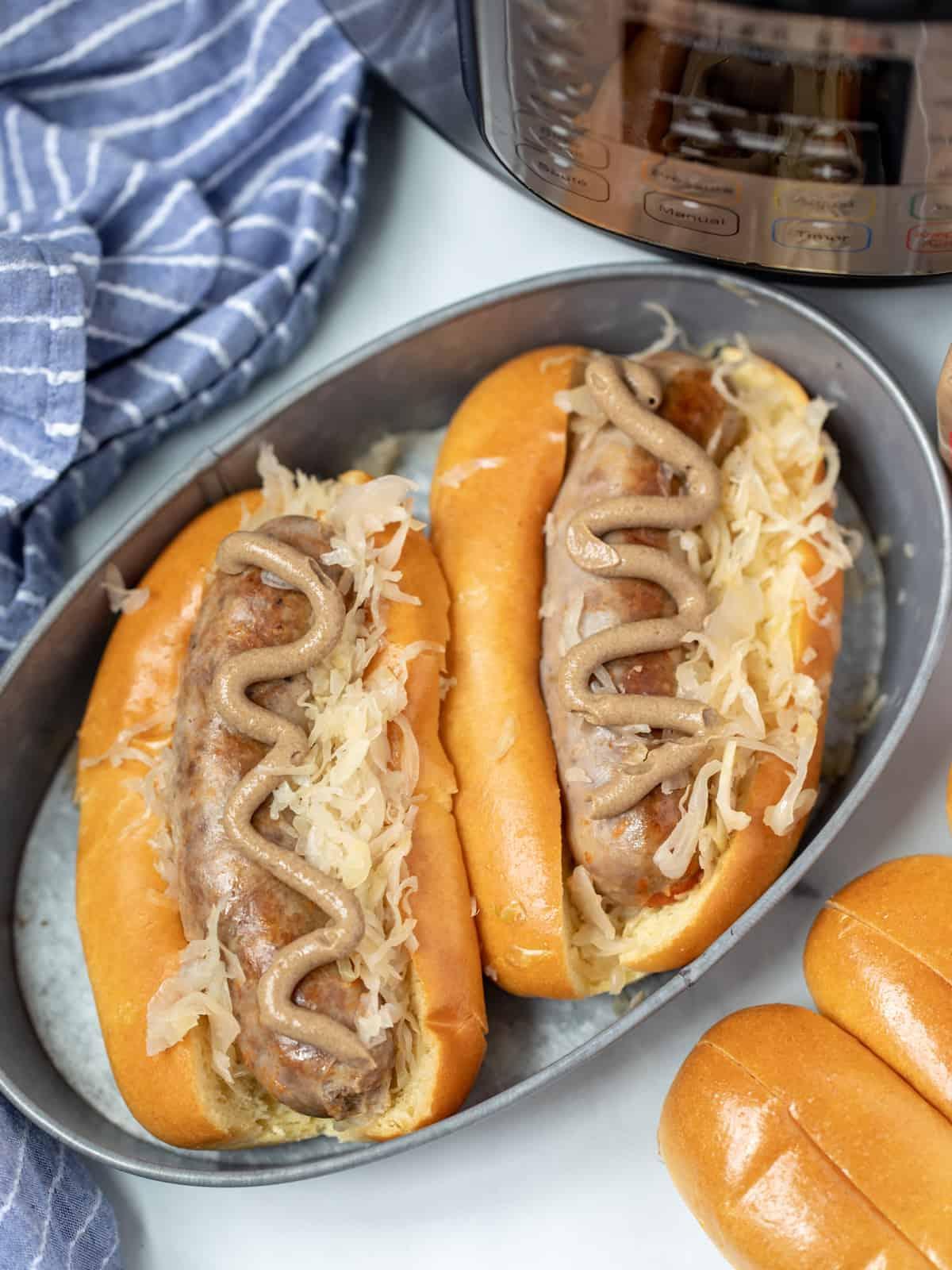 2 brats in bun with mustard and sauerkraut next to instant pot.