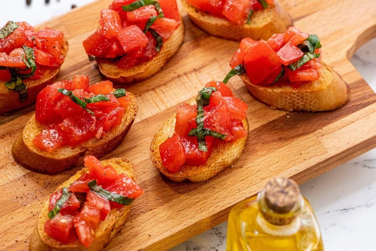 Wooden tray with prepared tomato bruschetta.