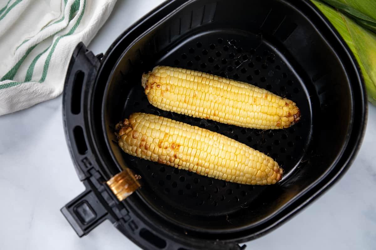 2 cooked ears of corn in basket of air fryer.