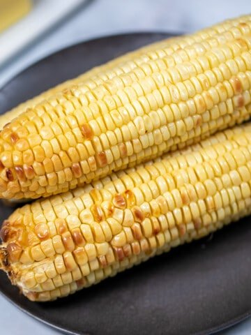3 ears of air fried corn on a black plate.