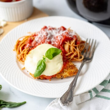 Air Fryer Chicken Parmesan on white plate served with side of spaghetti.