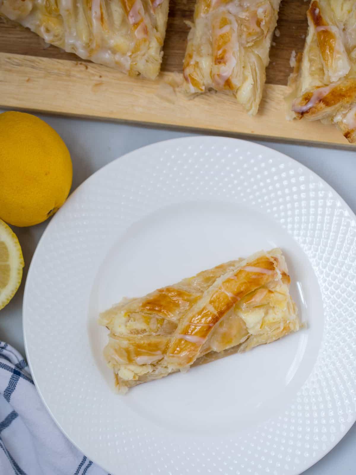 Slice of cream cheese danish on white plate.