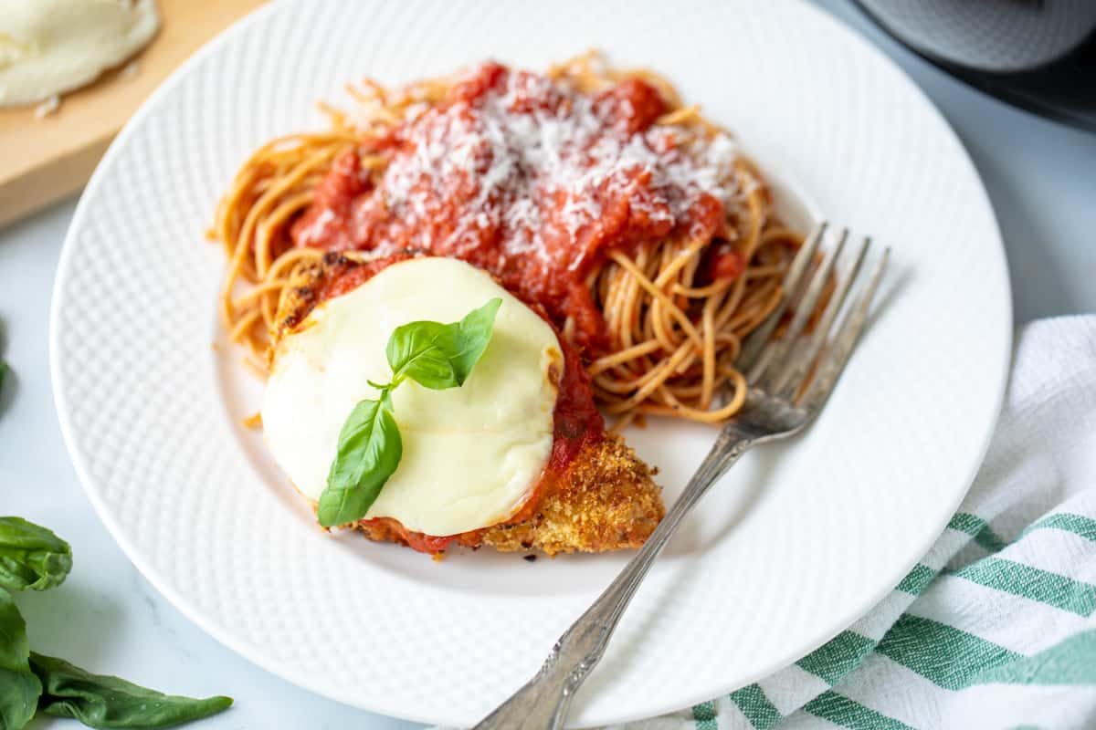 Air Fryer Chicken Parmesan on a plate with a side of spaghetti.