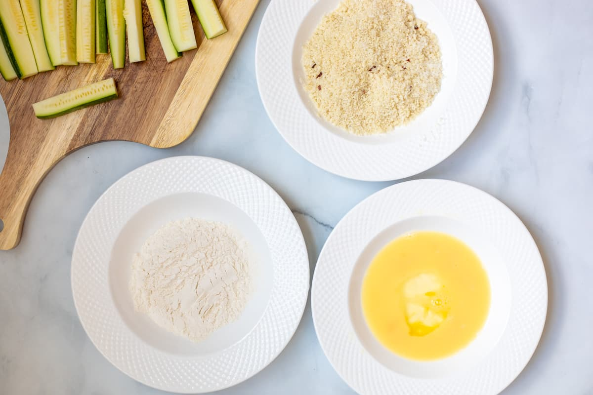 3 shallow white bowls showing breading station for zucchini fries.